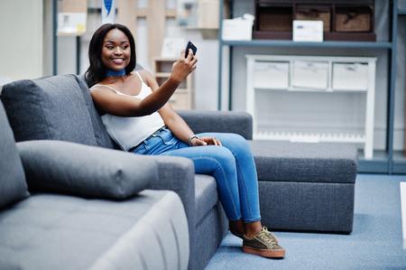 shopper: Portrait of a beautiful african american woman taking a selfie in the shop.
