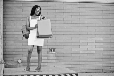 shopper: Portrait of a fantastic african american woman wearing sunglasses holds multicolored shopping bags outside the mall. Black and white photo. Stock Photo