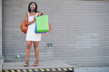 shopper: Portrait of a fantastic african american woman wearing sunglasses holds multicolored shopping bags outside the mall.