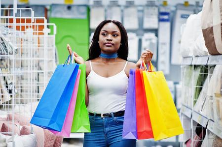 아름 다운 아프리카 계 미국인 여자 저장소에서 여러 가지 빛깔 된 쇼핑 가방을 들고. 스톡 콘텐츠