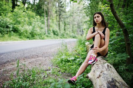 Sport girl at sportswear having rest in a green park after training at nature. A healthy lifestyle. Stock Photo