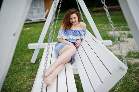 lit image: Portrait of a stunning young girl wearing blue marine-styled dress sitting on swings on the lakeside. Stock Photo