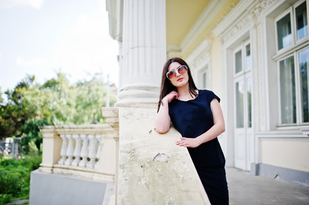 Brunette girl at black dress, sunglasses posed against old vintage house, at street of city. Stock Photo