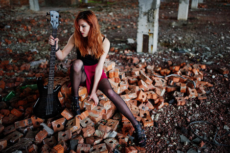to thrash: Red haired punk girl wear on black and red skirt, with bass guitar at abadoned place. Portrait of gothic woman musician.