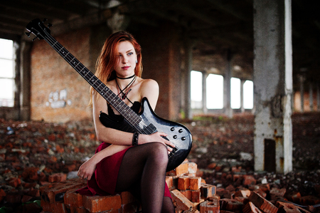 Red haired punk girl wear on black and red skirt, with bass guitar at abadoned place. Portrait of gothic woman musician.
