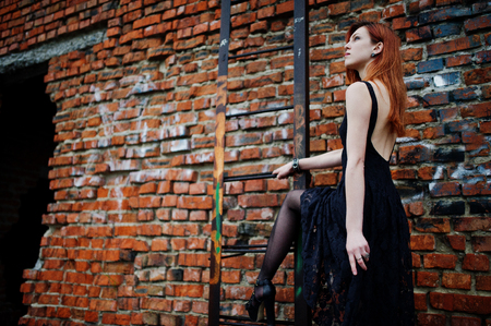 to thrash: Red haired punk girl wear on black dress at the roof against brick wall with iron ladder.