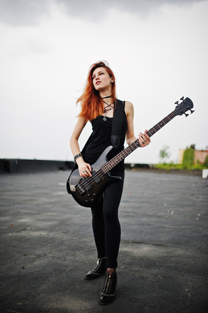 to thrash: Red haired punk girl wear on black with bass guitar at the roof.