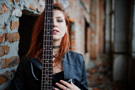 Red haired punk girl wear on black with bass guitar at abadoned place. Portrait of gothic woman musician. Close up face of blackness person with guitar riff. Stock Photo