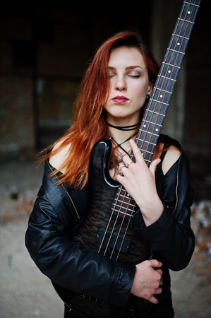 to thrash: Red haired punk girl wear on black with bass guitar at abadoned place. Portrait of gothic woman musician.