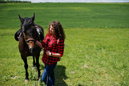 Young pretty girl stay with horse on a field at sunny day. Stock Photo