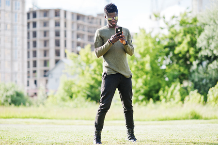 Attractive young african american guy wearing sunglasses uses his smartphone in the park with buildings in the background.