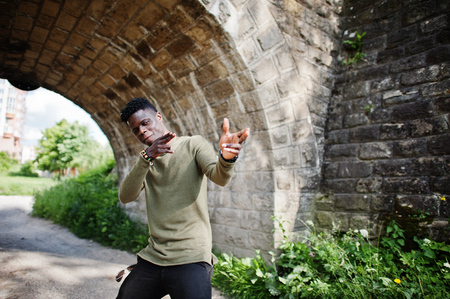 Handsome young african american guy in casual clothing posing and walking in the tunnel.