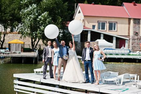 Wedding couple, groomsmen and bridesmaids having fun with balloons on wharf. 版權商用圖片