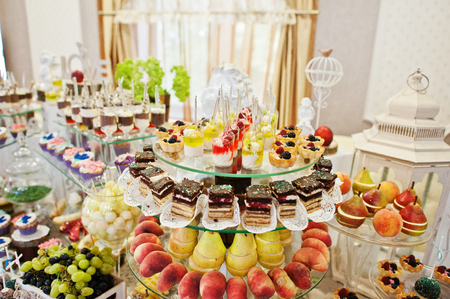 Gorgeous-looking wedding table with various beverages, delicious dishes, fruits and decorations.