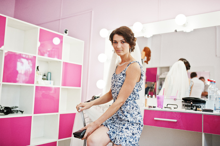 Beautiful bride getting ready for her wedding in a makeup and hair beauty salon