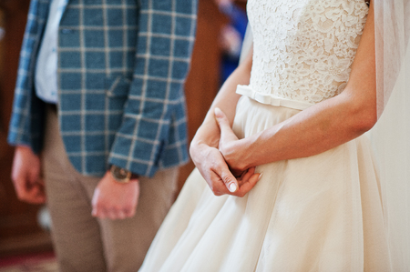 commit: Close-up photo of brides and grooms hands in the church on their wedding ceremony. Stock Photo