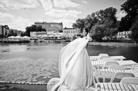 enchanting: Beautiful couple walking on a wharf on a sunny wedding day. Black and white photo.