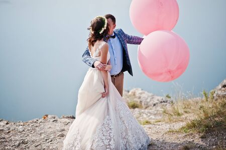 Gorgeous bride and groom having great time standing on the precipice with a view of a lake with balloons in their hands on their wedding day.