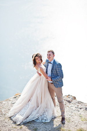 Fantastic wedding couple standing on the edge of rocky precipice with a perfect view of lake on the background. Stock Photo
