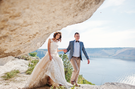 Gorgeous wedding couple posing next to the cave with breathtaking view of lake in the background.