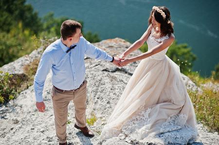 환상적인 웨딩 커플 바위 절벽 배경에 호수의 완벽 한보기의 가장자리에 서 서.