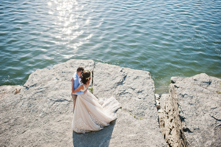 Newly married couple dancing on the rocky cliff with a view of a lake in the background on their wedding day.
