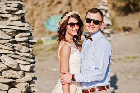 Gorgeous wedding couple standing next to the pile of stones on the lake shore.
