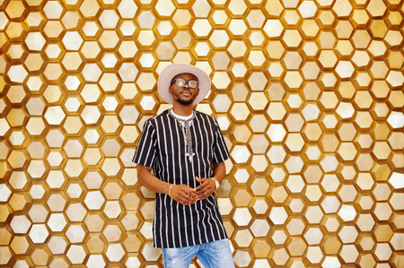Attractive mature african american man in stylish clothing posing next to the golden wall. Stock Photo