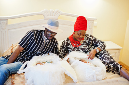 Gorgeous african american family consisting of traditionally dressed parents and little kids posing in the bedroom.