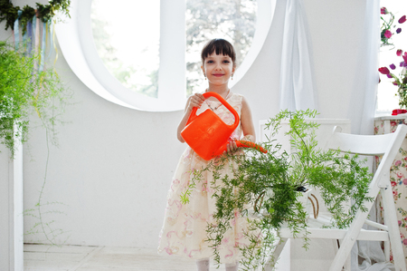 Small beautiful girl in a dress watering plants.