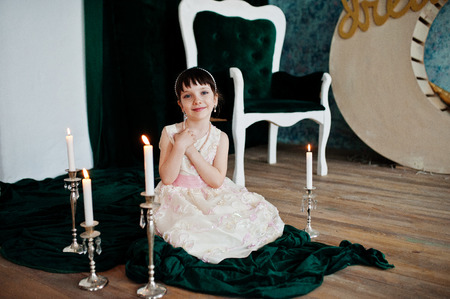 Portrait of a small cute girl in a lovely dress posing with the candlestick in a studio.
