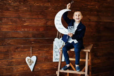 Portrait of a small handsome boy in official clothes posing on the ladder in the studio with moon and wooden wall. Stock Photo