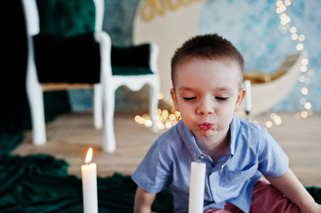 Portrait of an adorable little boy in official clothing posing with candlestick.