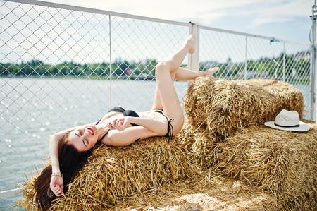 portrait d & # 39 ; une belle fille en bikini noir bikini posant sur la balle de foin avec un chapeau par le lac