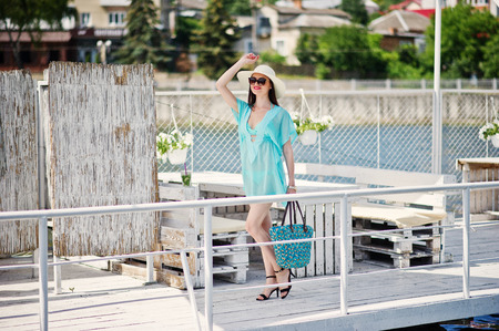 Lovely girl wearing transparent dress, hat and sunglasses walking on the quay by the lake with her bag. Stock Photo