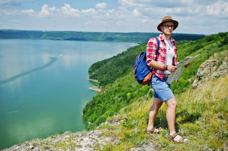 lost lake: Stylish man wearing checkered red shirt and a hat posing with a map in the nature with a lake on the background. Stock Photo