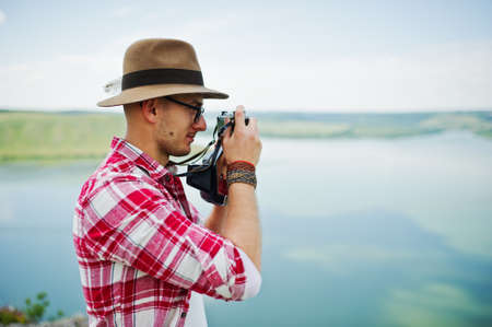 filmmaker: Portrait of a stunning man in casual clothing with a hat posing with an old camera on the rock with a lake on the background. Stock Photo
