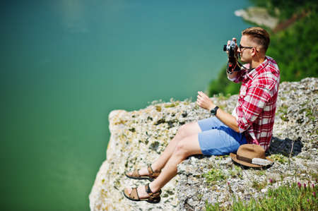 super man: Portrait of a stunning man in casual clothing with a hat posing with an old camera on the rock with a lake on the background. Stock Photo