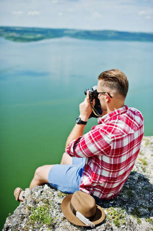 Portrait of a stunning man in casual clothing with a hat posing with an old camera on the rock with a lake on the background. Stock Photo