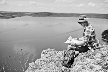 lost lake: Stylish man wearing checkered red shirt and a hat posing with a map in the nature with a lake on the background. Black and white photo.