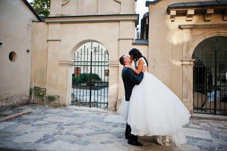 Splendida giovane coppia di nozze baciare sulla strada della città vecchia con grande odore
