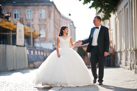Amazing young attractive newly married couple walking and posing in the downtown with beautiful and ancient architecture on the background on their wedding day.