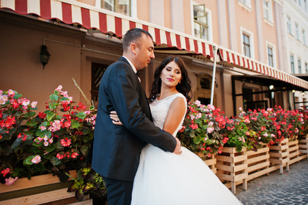 Amazing young attractive newly married couple walking and posing in the downtown with beautiful architecture and flowers on the background on their wedding day.