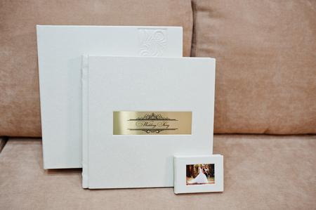 세련 된 흰색 가죽 결혼식 사진첩 또는 소파에 황금 비문 서와 함께 사진 앨범.