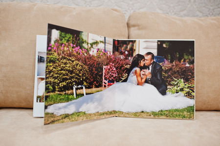 Pages of wedding photobook or wedding album on the sofa with cushions on the background.