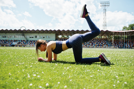 Portrait of a beautiful woman in sportswear stretching her muscles in the stadium. Stock Photo