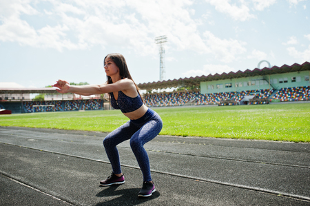 Portrait of a gorgeous girl doing squats in the stadium. Stock Photo