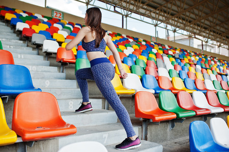 Active young woman running up on stairs in the stadium. Foto de archivo