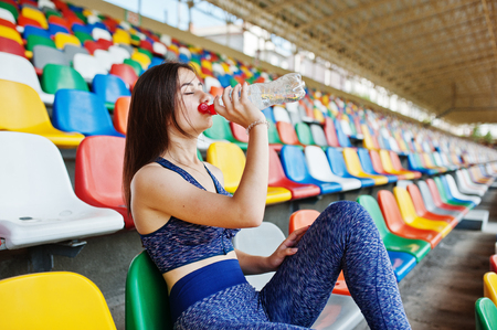 Portrait of a pretty woman in sportswear sitting and drinking water in the stadium. Stock Photo