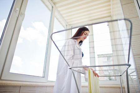 魅力的な女性が身に着けている下着やシャツは、バルコニーに洗濯物を干します。